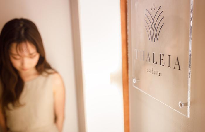 女性と入口のロゴが映っている写真